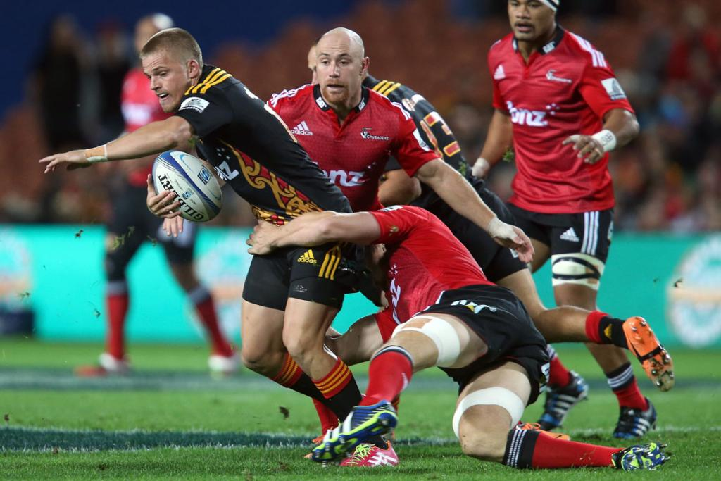 Gareth Anscombe of the Chiefs looks for support in the tackle of Kieran Reid of the Crusaders.