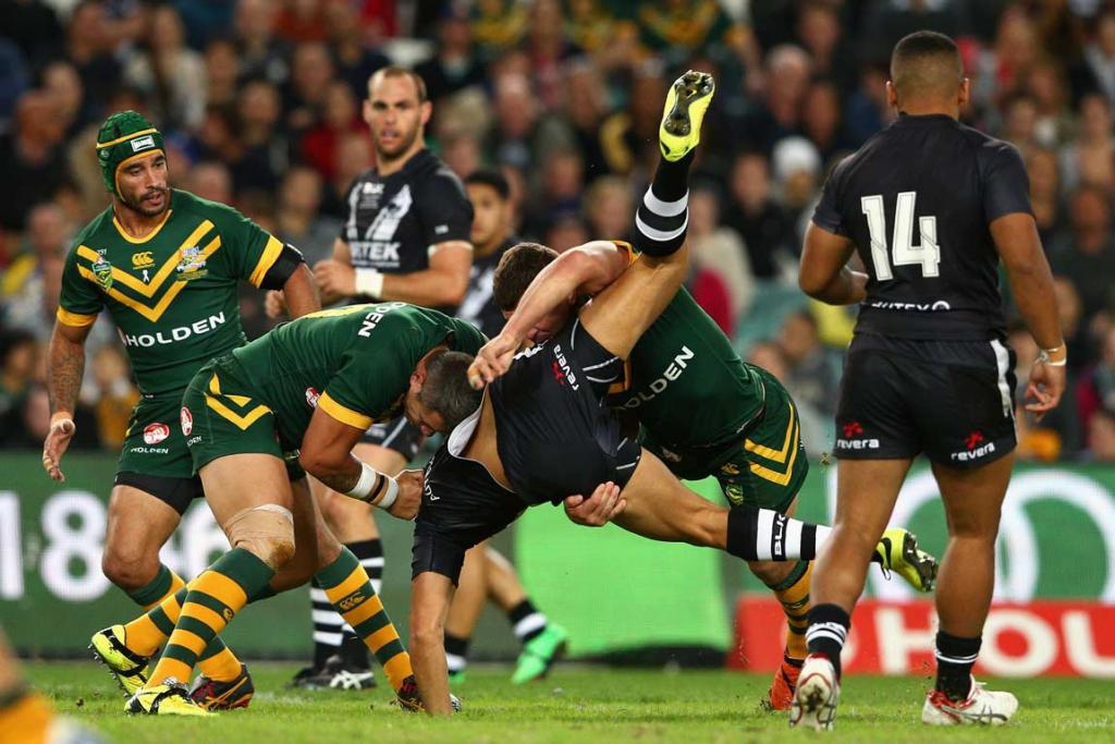 Kiwis centre Dean Whare is dumped in a three-man Australian tackle.