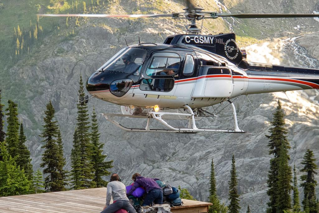 Guests arrive by helicopter at Durrand Glacier Chalet, owned by Ruedi and Nicoline Beglinger, seen here holding down gear against the chopper winds.
