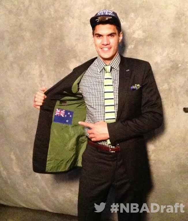 Steven Adams holds open his jacket showing the NZ flag sewn onto the lining.