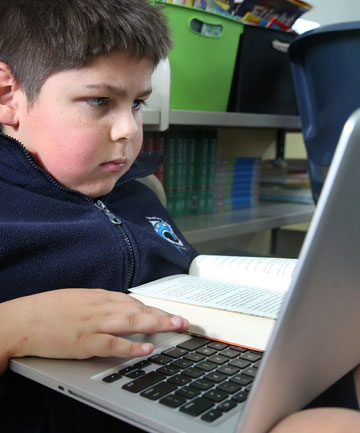 TECHNICALLY FOCUSED: Sam White, 10, combines the old way of learning with the modern way.