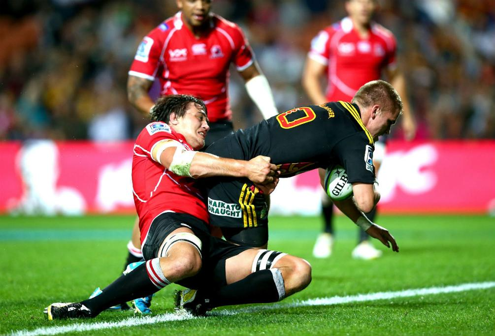 Gareth Anscombe of the Chiefs scores a try in the tackle of Franco Mostert of the Lions.