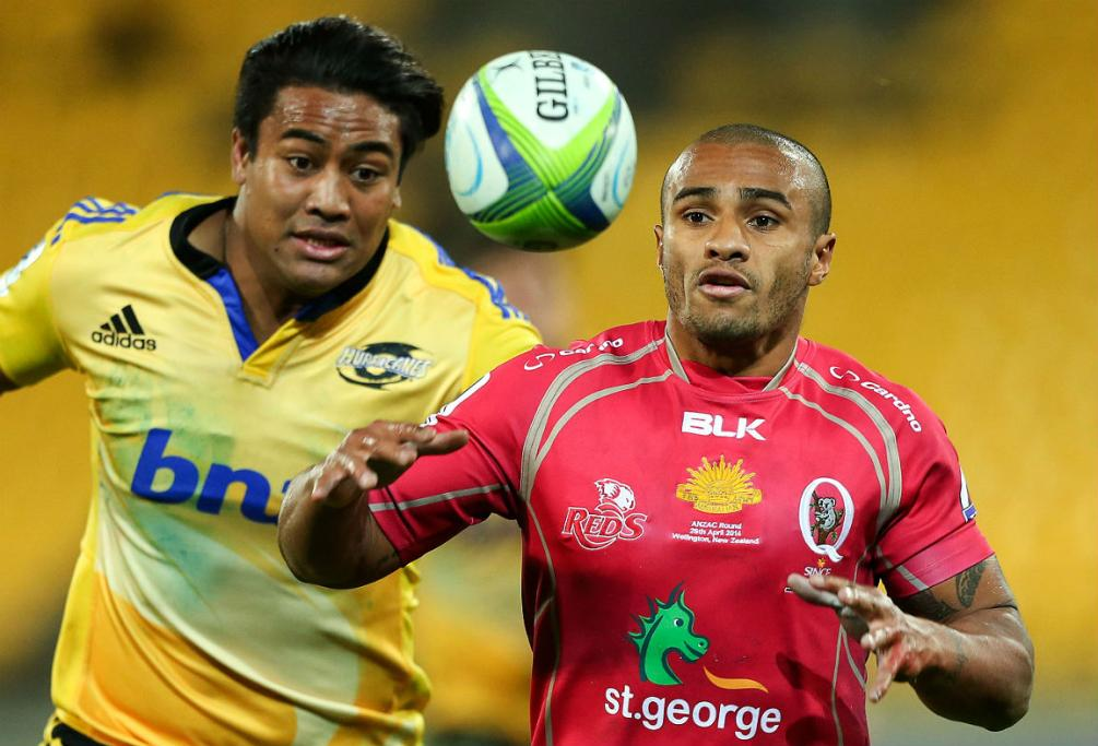Reds halfback Will Genia, right, tries to get to the ball ahead of Hurricanes winger Julian Savea.