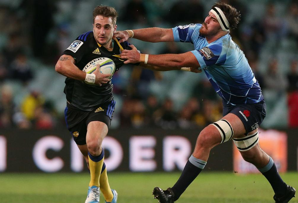 Andre Taylor of the Hurricanes evades the tackle of Kane Douglas of the Waratahs.