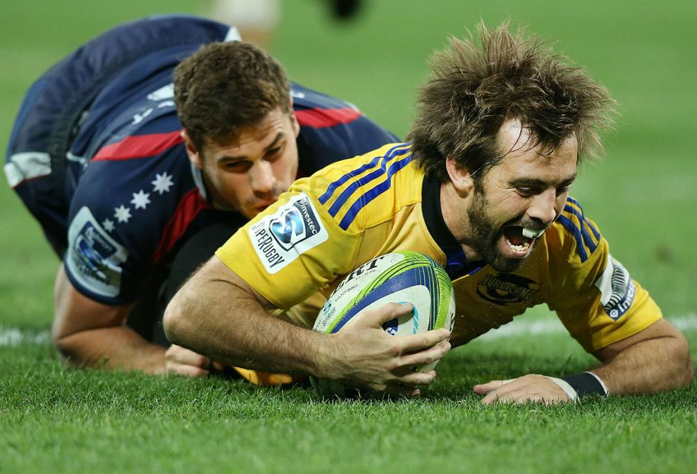 Conrad Smith of the Hurricanes scores a try despite the efforts of the Rebels' Tom English.