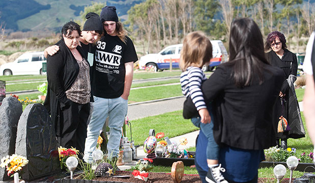 BIRTHDAY SADNESS: Angela Middlemiss stands with her sons Gordon Booker, 19, and Leighton Booker, 18, at the unveiling of her son Nathan Booker's headstone.