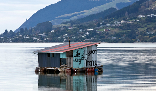 "DEFIANT PROCLAMATION: Paul Jepson's houseboat, due to be removed from Nelson Haven by the city council next week, with ""Life will go on long after money'' painted on the structure's side."