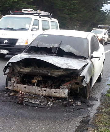 BURNT OUT: A car which caught fire, blocking traffic on SH58.