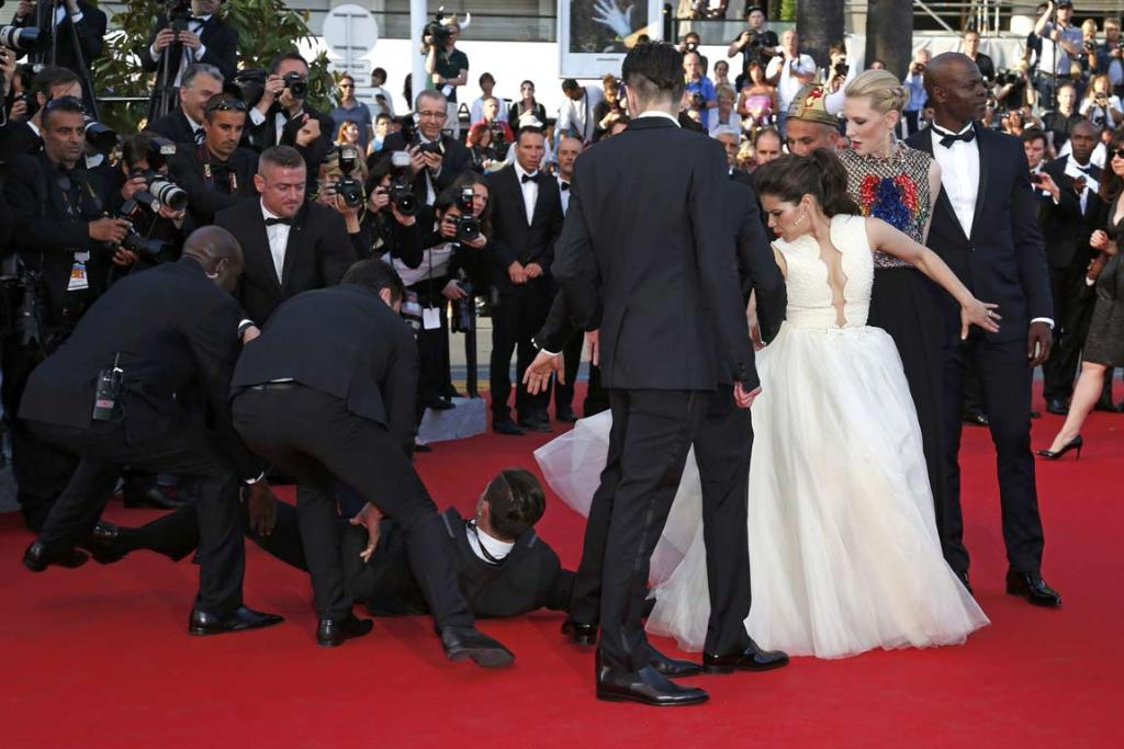 A man is arrested by security as he tries to slip under the dress of actress America Ferrera as she poses on the red carpet after arriving for the screening of the film How to Train Your Dragon 2 at the 67th Cannes Film Festival in Cannes.