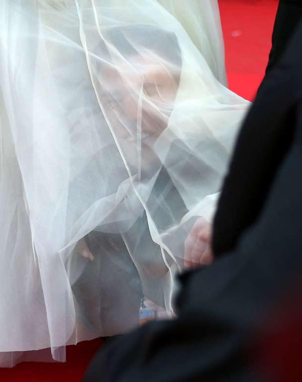 A man under America Ferrera's dress at the How To Train Your Dragon 2 premiere during the 67th Annual Cannes Film Festival.