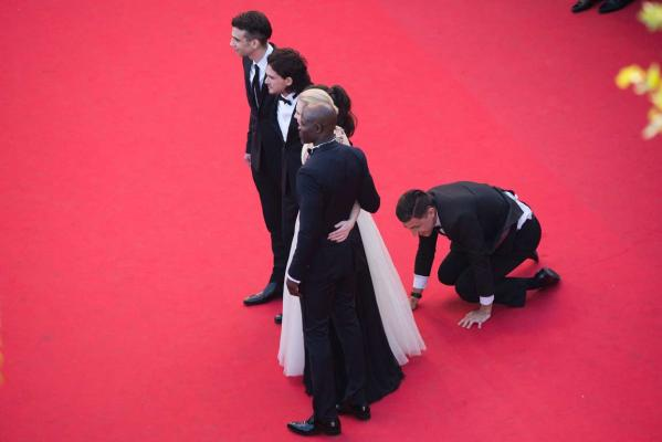 A man invades the red carpet as Jay Baruchel, Kit Harington, America Ferrera, Cate Blanchett and Djimon Hounsou pose at the How To Train Your Dragon 2 premiere during the 67th Cannes Film Festival.