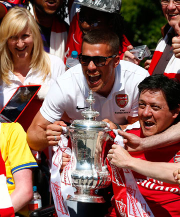 FAN FAVOURITE: Lukas Podolski celebrates Arsenal's FA Cup with fans.