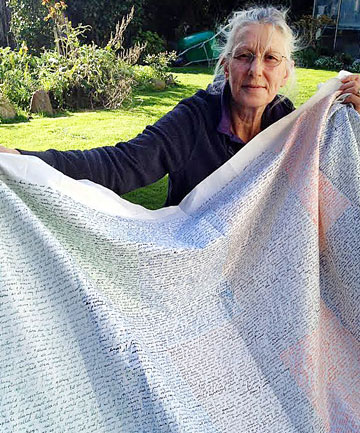 "Opunake artist Viv Davy with part of her masters project - a daily ""journal"" written on cloth in different coloured ink, recording mundane domestic activities."