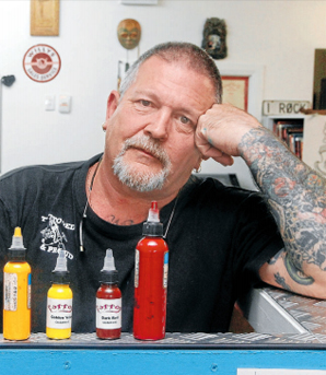 BIG WORRY: Willy Wills believes there should be strict regulations for tattoo artists partly because some artists use carcinogenic ink. He is pictured with the tall ink bottles he uses and the small ones he is concerned about.