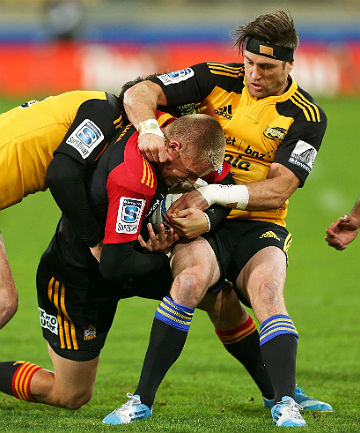 TOUGH GOING: Chiefs pivot Gareth Asncombe is wrapped up by the Hurricanes defence including All Black Cory Jane, right.