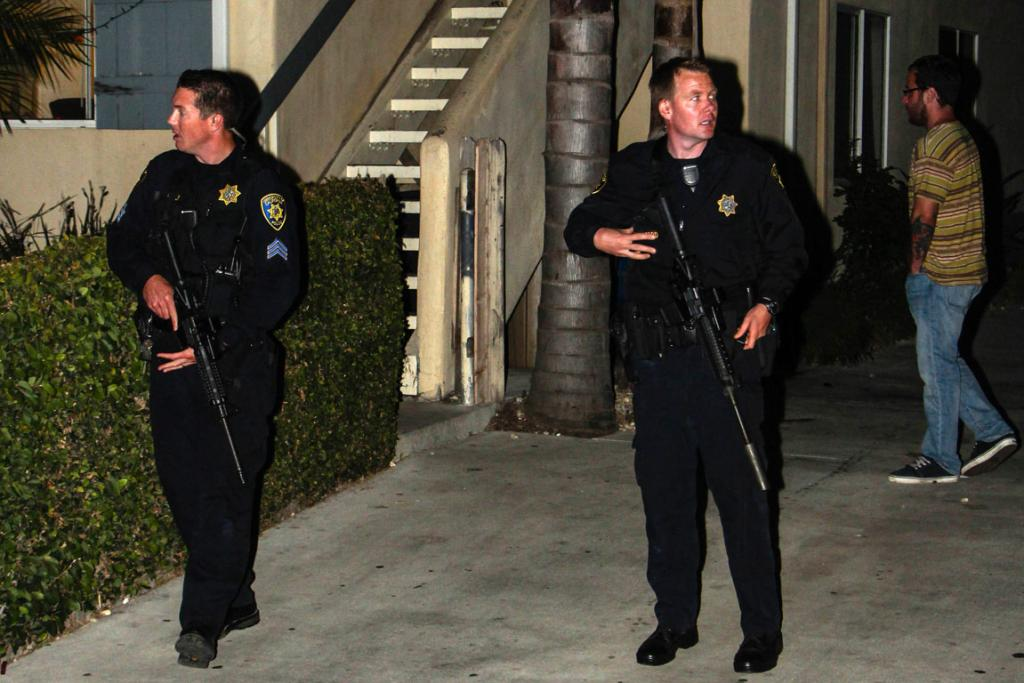 Police walk through an apartment complex following the shooting.