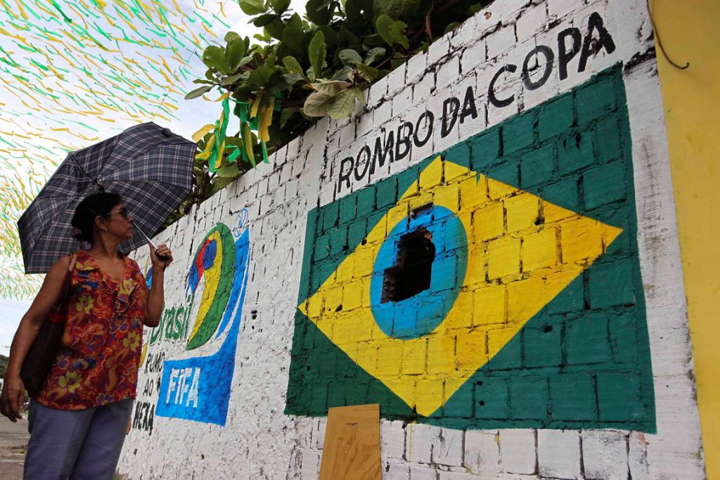A pedestrian looks at a graffiti in protest against the 2014 World Cup that shows the Brazilian flag painted around a hole in a wall in Manaus.
