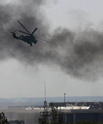 FIGHTING BACK: A Ukrainian helicopter Mi-24 gunship fires its cannons against rebels at the main terminal building of Donetsk international airport.
