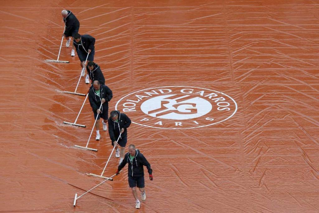 Court crew sweep water off the covers during a delay on day two at Roland Garros.