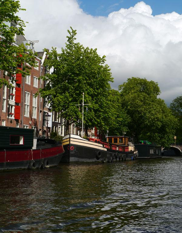 It's horribly touristy but you have to take a tour along the canals during your stay in Amsterdam.
