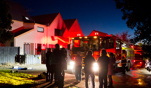 ON THE SCENE: Residents watch on as firefighters attend a house fire on Sovereign St in Nelson on Monday night.