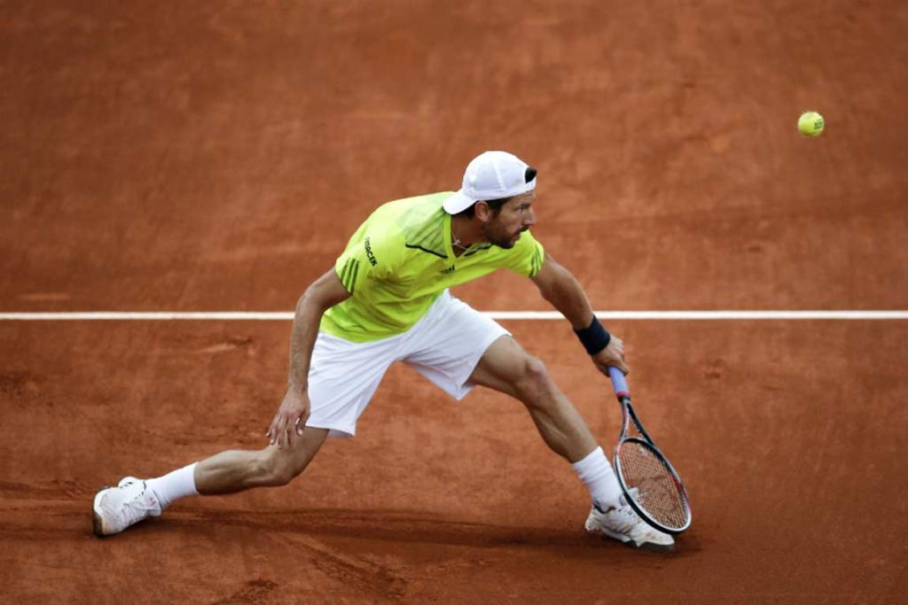 Austria's Jurgen Melzer stretches to hit a forehand against Jo-Wilfried Tsonga.