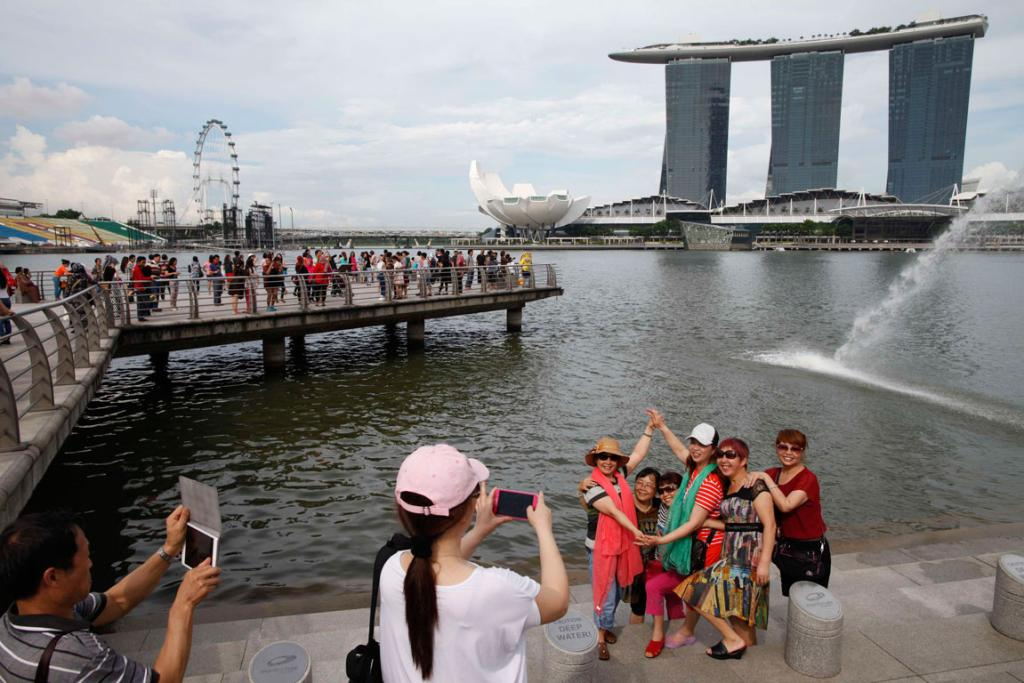 Chinese tourists pose for photos with the Marina Bay Sands casino and hotel in the central business district of Singapore.