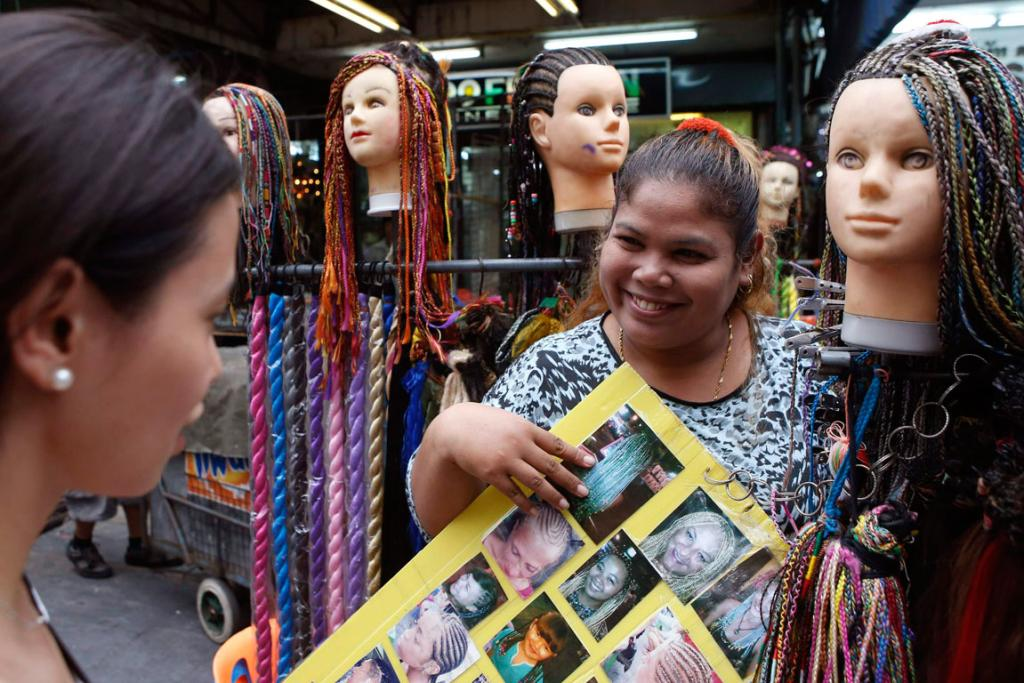 A hairstylist shows braid samples to a woman at an outdoor beauty parlour in a tourist district of Khao San Road in Bangkok.