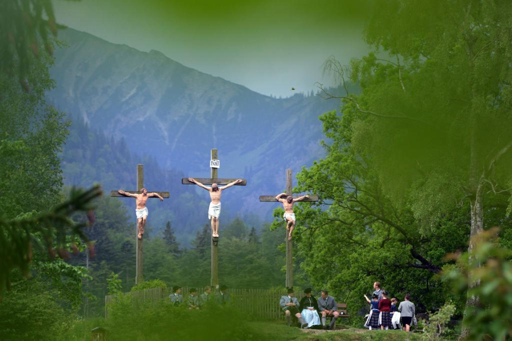 Pilgrims in traditional Bavarian folk costumes stand beneath three crosses on the Kalvarienberg-mountain and follow an outdoor mass to celebrate Ascension (in German called Christi Himmelfahrt) at the open-air altar at Birkensteinnear Fischbachau, Germany.