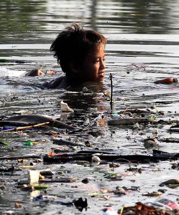 MESS: A boy wades in a polluted river to collect recyclable items in Bacoor town, south of Manila.