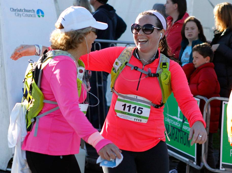 Christchurch airport marathon runners celebrate after crossing the finish line.