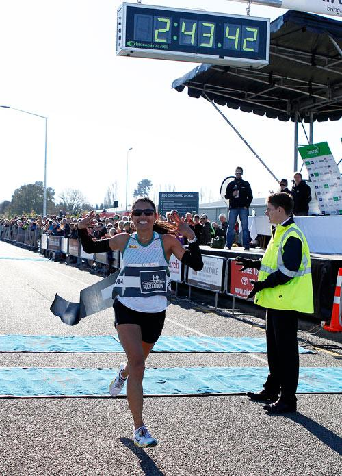 Jubilent womans marathon winner Liza Hunter-Galvin crossing the finish line of the Christchurch airport marathon.