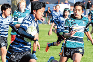 EYES ON THE LINE: Under-13 Town team winger, Renz Narvadez, makes a determined run late in the second half of their match against Country. Coming in for the tackle is Zane Matangi. bbPhotos: