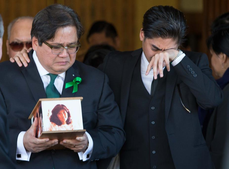 Antonio Gotingco is comforted by his tearful son as he leaves the memorial service holding the ashes of his wife, Blessie Gotingco.