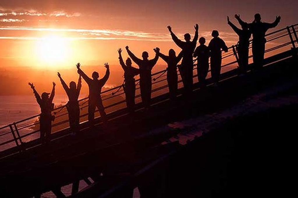 Climbers cheer their efforts at the top of the bridge while the sun rises behind them.