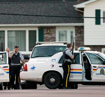 MEN DOWN: Police officers take cover behind their vehicles after three Royal Canadian Mounted Police were shot in Moncton, New Brunswick.