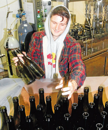 GLASS ACT: Hunter's Wines bottling worker Sam Carter manually loads the bottling plant with glass bottles ready to be sterilised and filled with 2014 vintage sauvignon blanc.