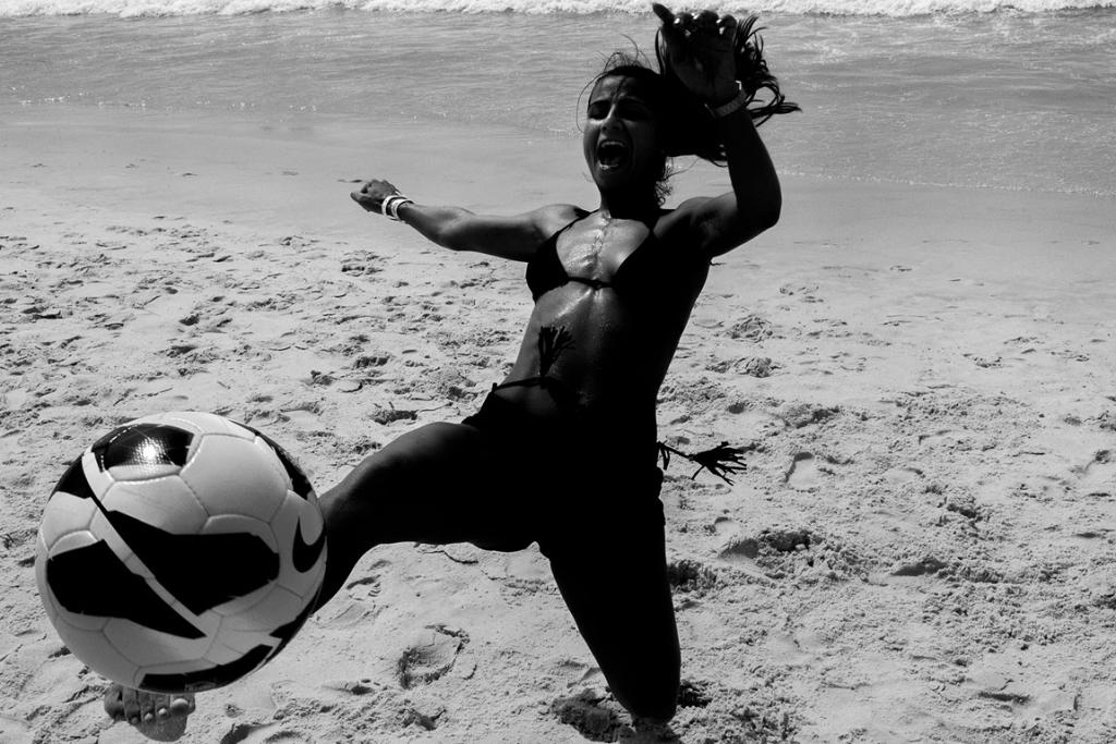 "A woman plays ""altinho"" (loosely translated as ""little height""), a soccer game played at the beaches of Rio de Janeiro, in which the ball can't touch the sand."