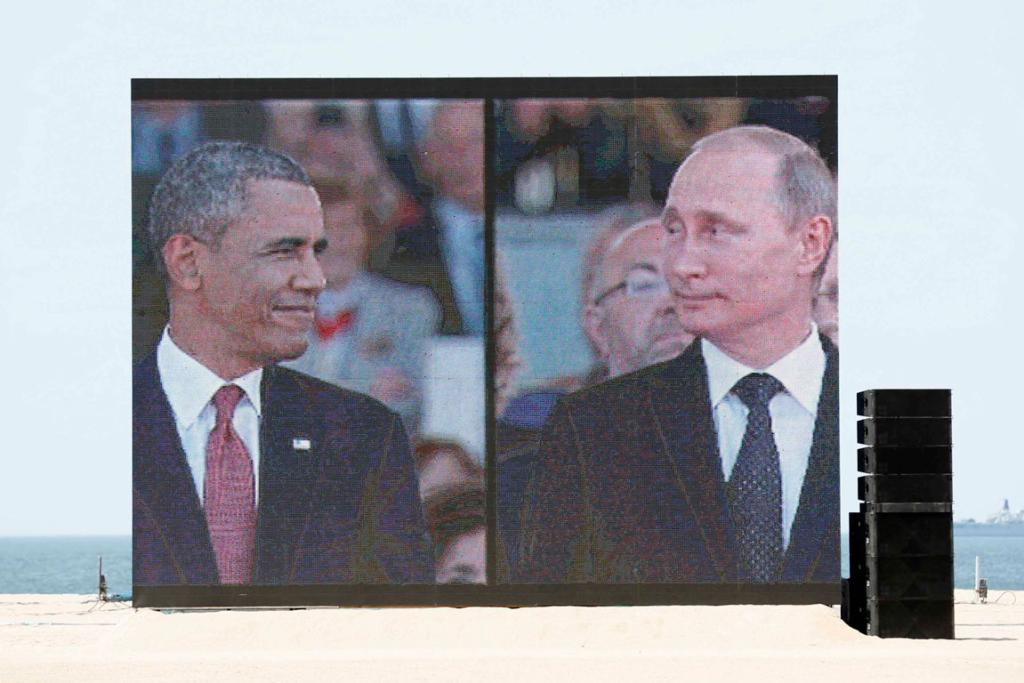 CAUGHT ON CAMERA: Laughter erupted in the crowd at Sword Beach when pictures of Barack Obama and Vladimir Putin were projected together on a big screen.
