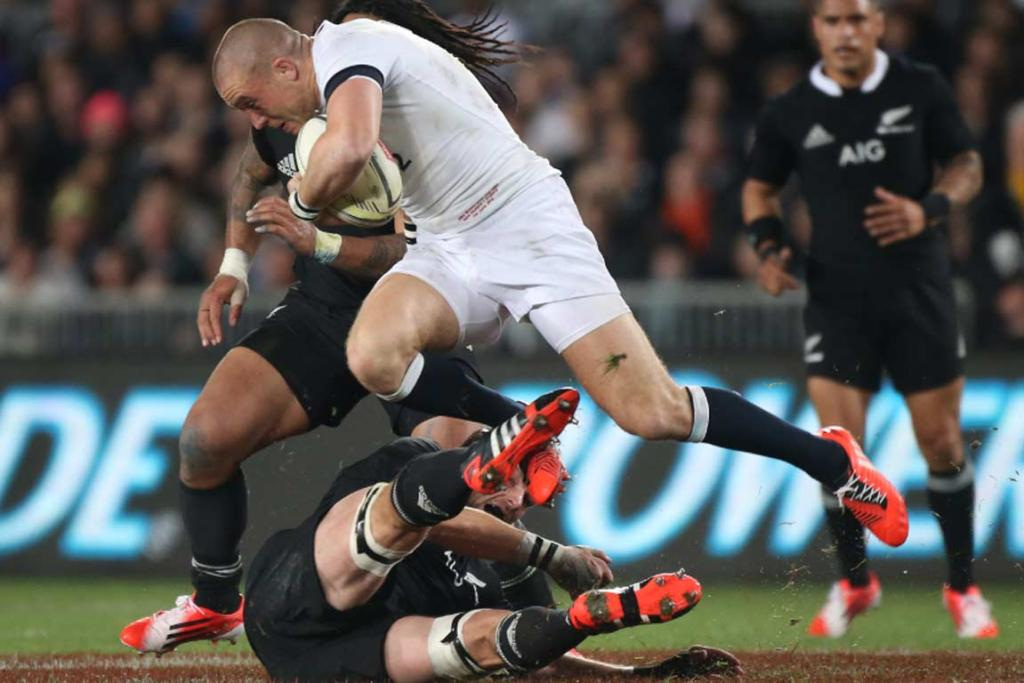 England's Mike Brown knocks Richie McCaw to the ground.