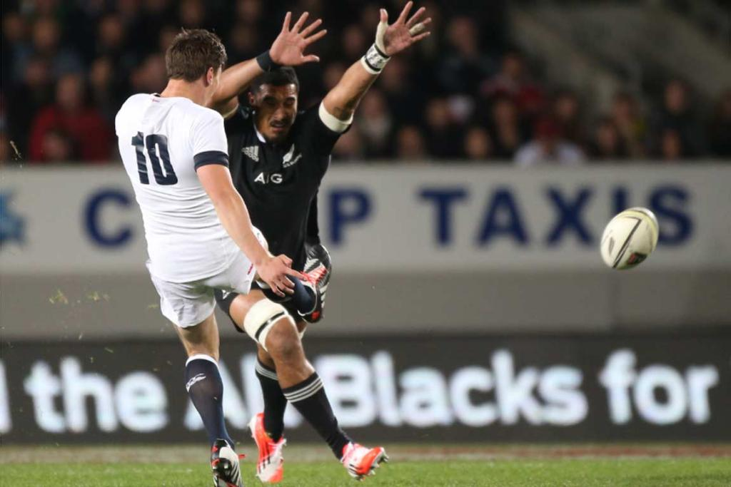 England No 10 Freddie Burns gets a clearing kick away under pressure from Jerome Kaino.