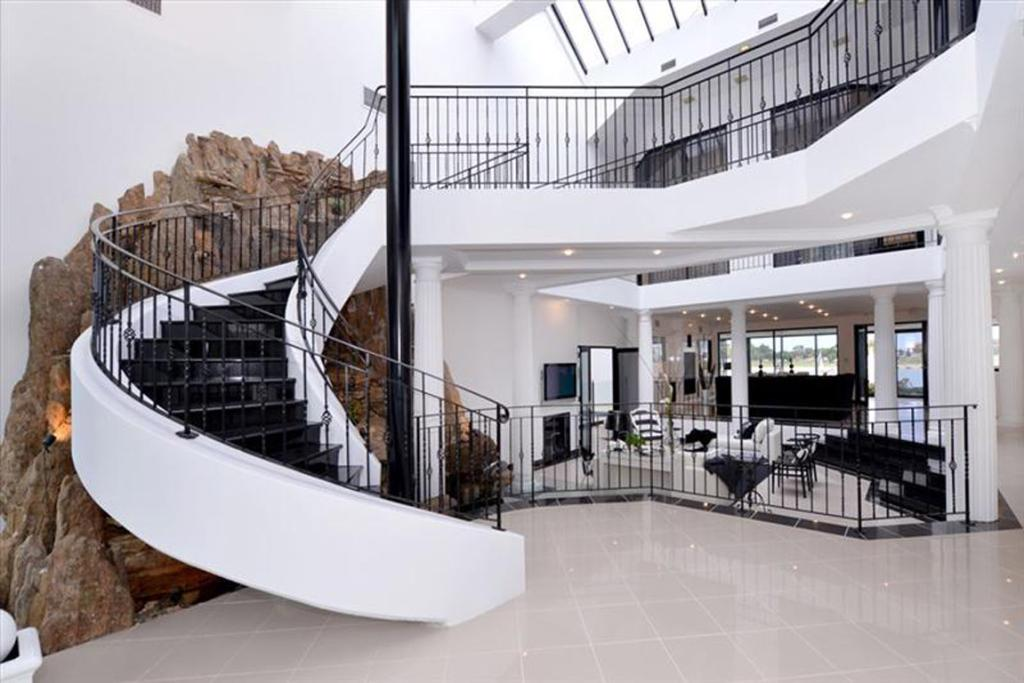 DRAMATIC INTERIORS: The modern behemoth features a dramatic marble foyer with a glass roof and winding staircase.