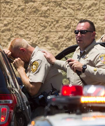 EMOTIONAL: A Metro police officer comforts a colleague outside the Wal-Mart.