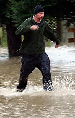 GUMBOOT WEATHER: Logan wades through deep water on Toppings Rd, near Sefton.