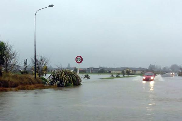 Cars battle flooded Rangiora roads.