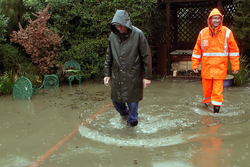 DELUGE STRIKES: John Crowe, right, with his father Derek Crowe, inspects the flooded garden.