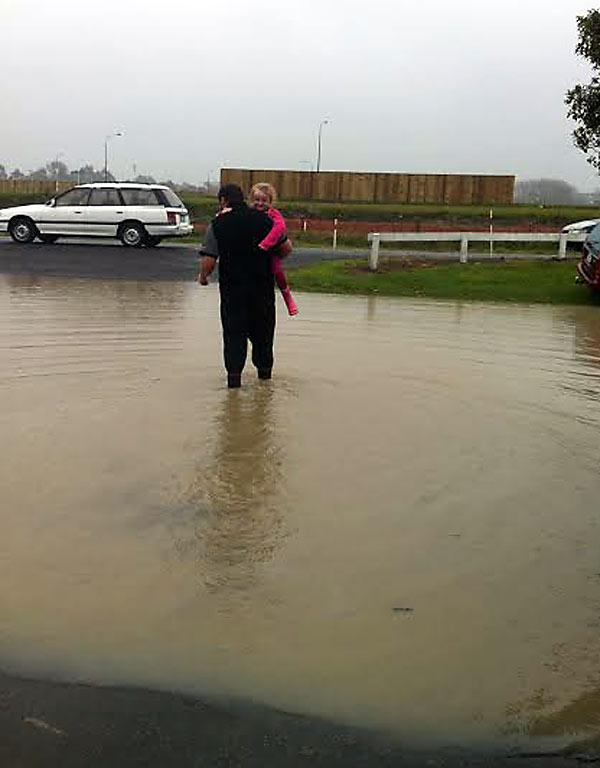 HITCHING A LIFT: Cassidy Earnshaw and Clinton Boyd wade away from their home in Island Rd, Kaiapoi.