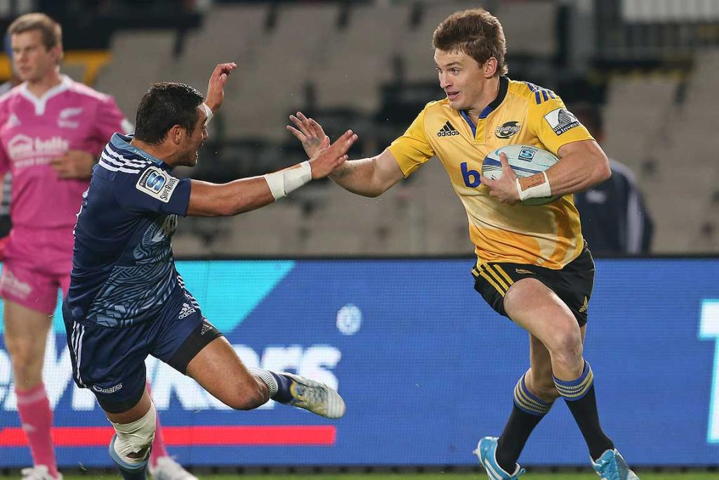 The Blues' Bryn Hall chases down Hurricane Beauden Barrett.