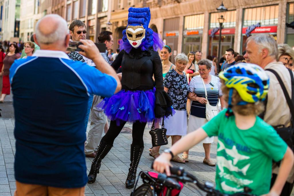 People take pictures during the Wave and Goth festival in the central shopping district of Leipzig.