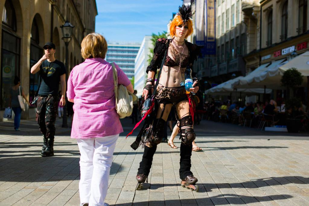 A woman takes a picture of a reveller skating through the city centre.